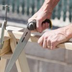 Folding Sawhorse with clamp being used to saw wood